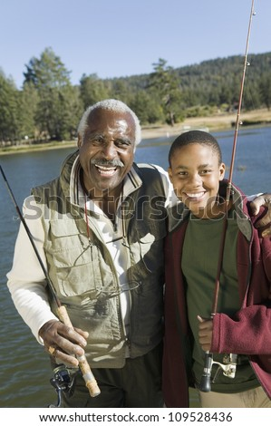 Portrait of happy senior man with grandson fishing on a sunny day - stock photo