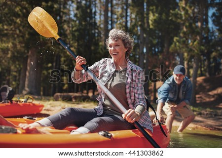 Portrait of happy senior paddling kayak in the lake with man supporting from behind. Mature couple enjoying a day at the lake. - stock photo