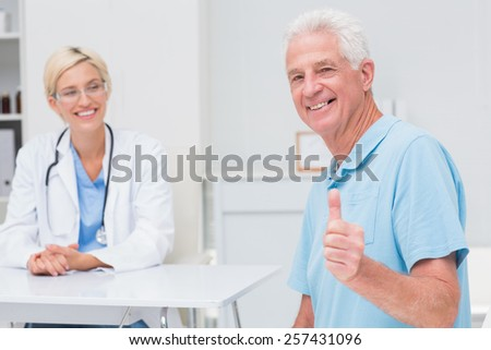 Portrait of happy senior patient gesturing thumbs up while doctor looking at him in clinic - stock photo