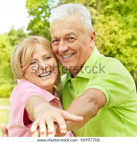 Portrait of happy senior woman and man enjoying in the park. - stock photo