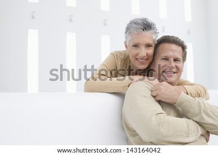 Portrait of happy senior woman embracing man from behind at home - stock photo