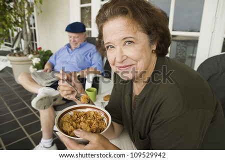 Portrait of happy senior woman having a bowl of cereals with man in background - stock photo