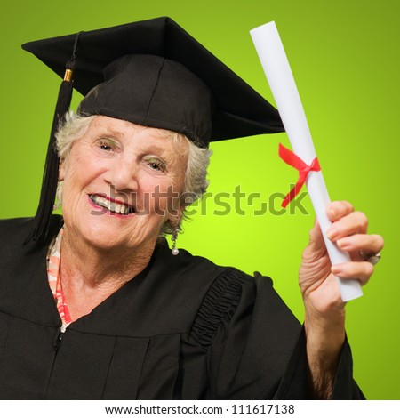 Portrait Of Happy Senior Woman Holding Graduation Degree Isolated Over Green Background