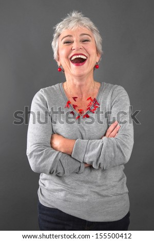 Portrait of happy senior woman laughing - stock photo