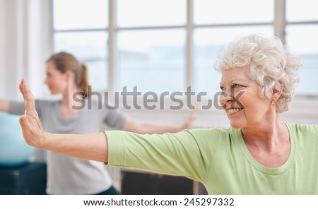 Portrait of happy senior woman practicing yoga at gym class. Elderly woman stretching her arms . - stock photo