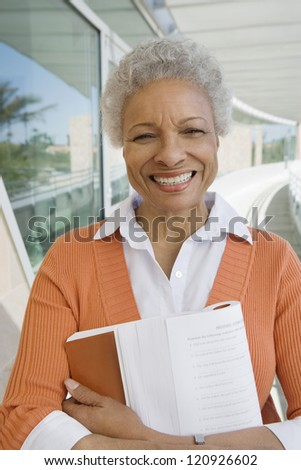 Portrait of happy senior woman standing with book - stock photo