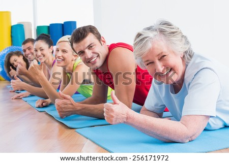 Portrait of happy senior woman with friends gesturing thumbs up while lying on exercise mats at gym - stock photo
