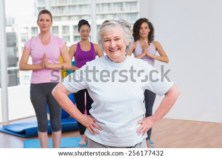 Portrait of happy senior woman with hands on hip standing against friends in gym - stock photo