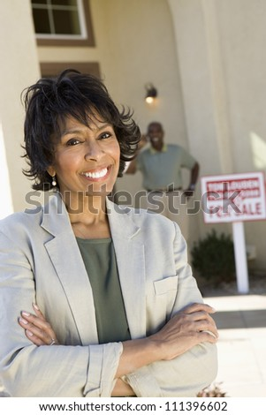Portrait of happy senior woman with man and 'For Sale' sign in background - stock photo