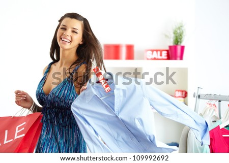 Portrait of happy shopper with bags and new shirt in clothing department - stock photo