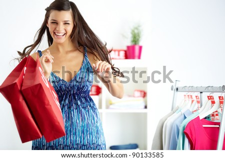 Portrait of happy shopper with bags laughing in clothing department - stock photo