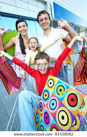 Portrait of happy shoppers with paper bags at shopping center - stock photo
