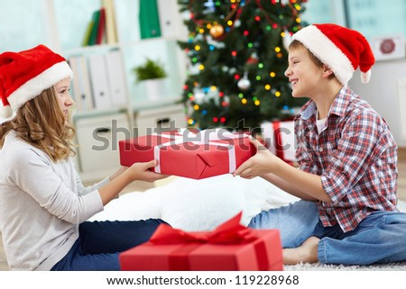 Portrait of happy siblings holding giftbox and looking at one another on Christmas evening