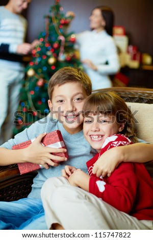 Portrait of happy siblings looking at camera on xmas eve with their parents on background - stock photo