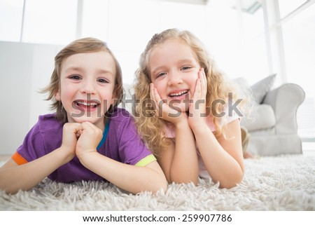 Portrait of happy siblings lying on rug at home - stock photo
