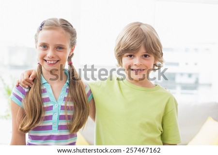 Portrait of happy siblings standing arm around at home
