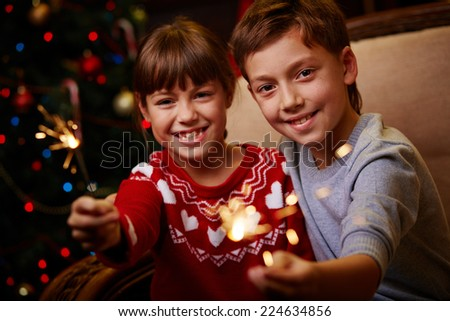 Portrait of happy siblings with Bengal lights celebrating Christmas - stock photo