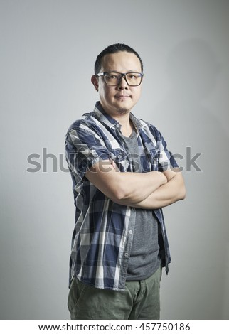Portrait of happy single mature 40s Asian man in casual , arms crossed ,smiling and standing over plain background with shadow. - stock photo