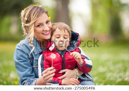 Portrait of happy single mother with her cute little son blowing dandelion - stock photo