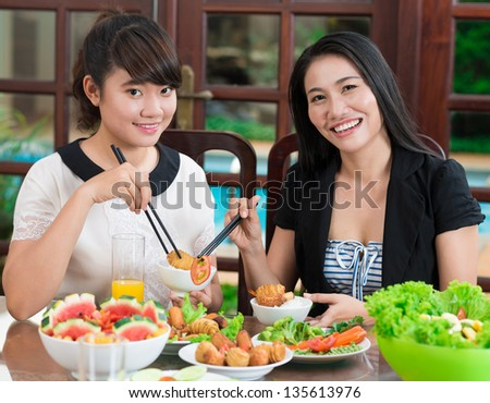 Portrait of happy sisters holding chop-sticks with the meal - stock photo