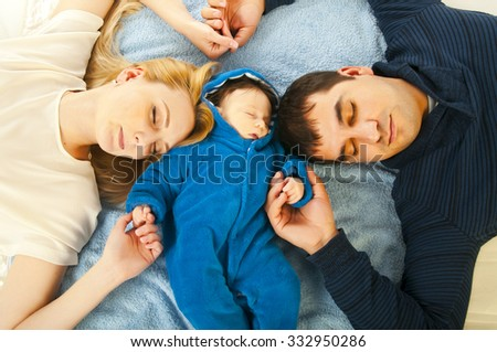 Portrait of happy sleeping young family with little kid holding hands