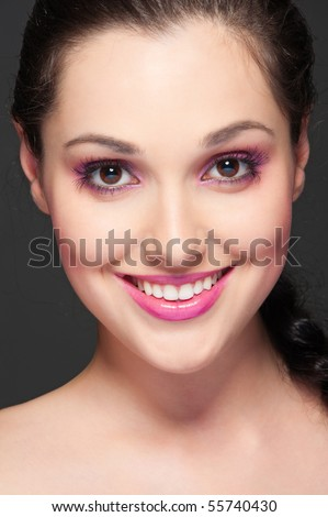 portrait of happy smiley brunette over dark background - stock photo