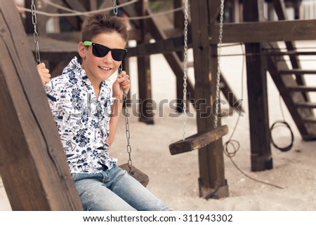 Portrait of happy smiling adolescent boy in sunglasses having fun on a swing at a summer playground. - stock photo