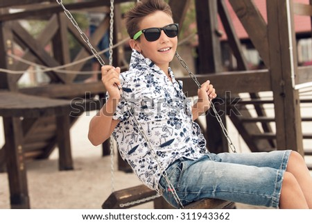 Portrait of happy smiling adolescent boy in sunglasses having fun on a swing at a summer playground.