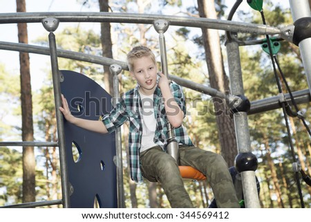 Portrait of happy smiling adolescent caucasian boy in having fun at a summer playground.