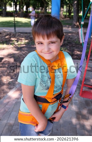 Portrait of happy smiling beautiful boy in safety equipment, outdoor shot - stock photo