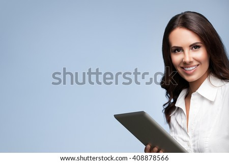 Portrait of happy smiling beautiful young brunette businesswoman using no-name tablet pc, over grey background, with blank copyspace area for slogan or text - stock photo