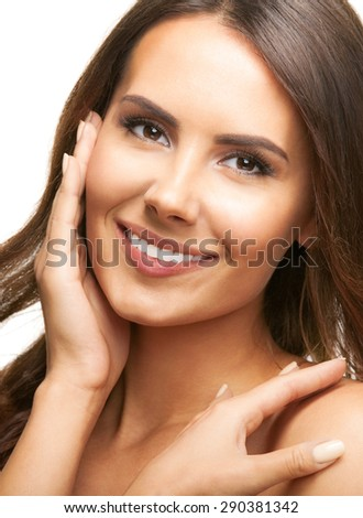 Portrait of happy smiling beautiful young brunette woman touching skin or applying cream, isolated over white background - stock photo