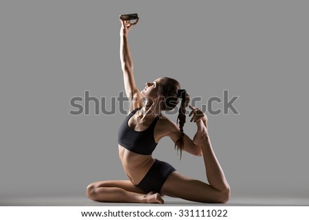 Portrait of happy smiling beautiful young fit woman in sportswear doing stretching sport exercise, sitting in One Legged King Pigeon Posture, taking selfie with mobile phone, studio, gray background - stock photo
