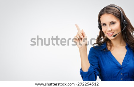 Portrait of happy smiling beautiful young support phone operator showing blank copyspace area for slogan or text, posing at studio against grey background - stock photo