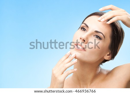 Portrait of happy smiling beautiful young woman touching skin or applying cream, over blue background, with copyspace for slogan or text message