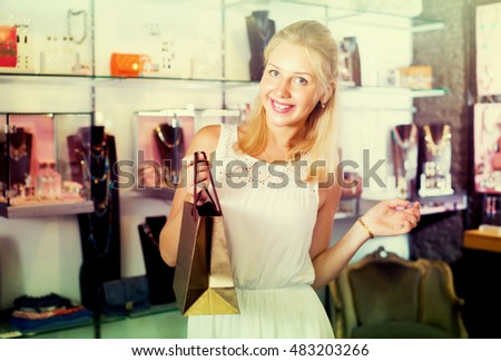 portrait of happy smiling blonde girl standing among showcases in bijouterie boutique