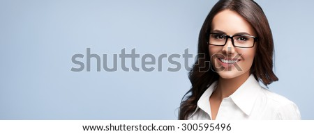 Portrait of happy smiling brunette businesswoman in glasses, over grey background - stock photo