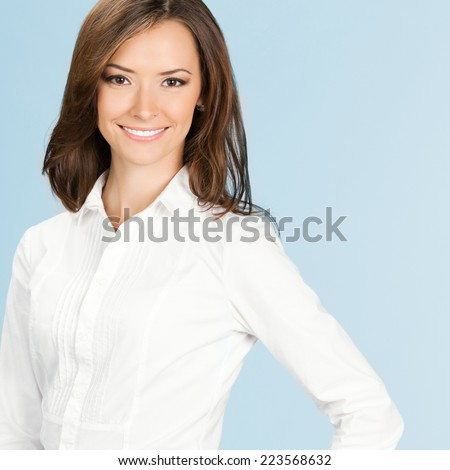 Portrait of happy smiling business woman, over blue background - stock photo