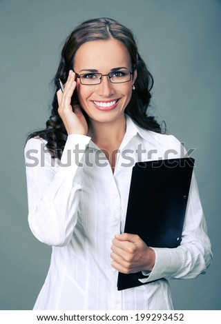 Portrait of happy smiling business woman with black folder, over gray background - stock photo