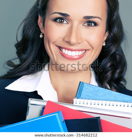 Portrait of happy smiling business woman with folders - stock photo