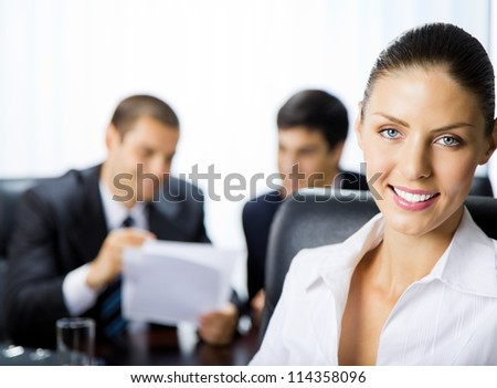 Portrait of happy smiling businesswoman and colleagues on background, at office - stock photo