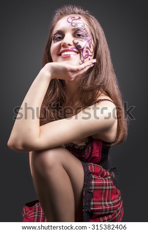 Portrait of Happy Smiling Caucasian Brunette Woman Painted with Facial Paint with Decorations. Posing Against Black Background. Vertical Image Composition - stock photo
