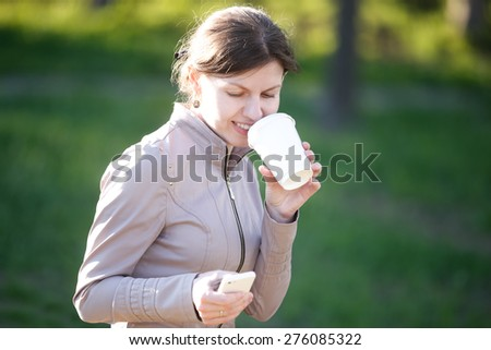 Portrait of happy smiling caucasian woman in park siting on the bench, drinking coffee to go, messaging, holding smartphone, using app - stock photo