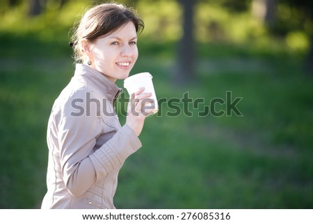Portrait of happy smiling caucasian woman in park siting on the bench, drinking coffee to go, copy space - stock photo