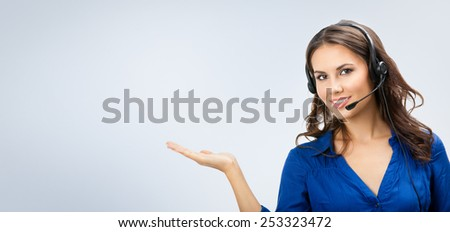 Portrait of happy smiling cheerful beautiful young support phone operator showing, with copyspace area - stock photo