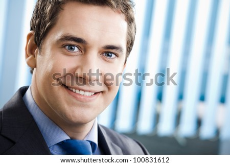 Portrait of happy smiling cheerful business man at office, with copyspace - stock photo