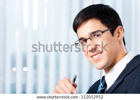 Portrait of happy smiling cheerful business man at office, with copyspace