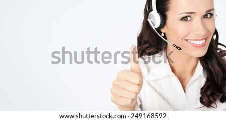Portrait of happy smiling cheerful customer support phone operator in headset showing thumbs up gesture, against grey background, with copyspace