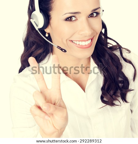 Portrait of happy smiling cheerful customer support phone operator or businesswoman in headset showing two fingers or victory hand sign gesture