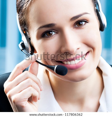 Portrait of happy smiling cheerful support phone operator in headset at office - stock photo